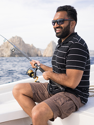 Smiling man on a boat with a fishing rod