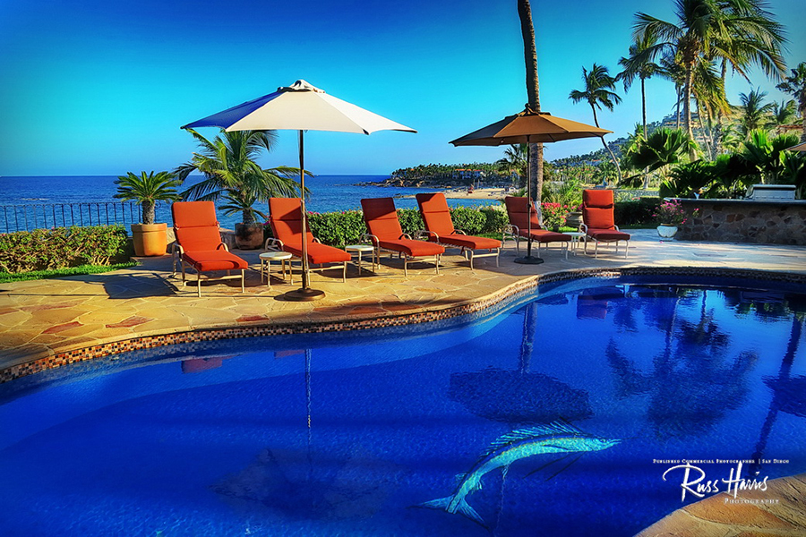 Blue bottom pool facing the ocean with red lounge chairs