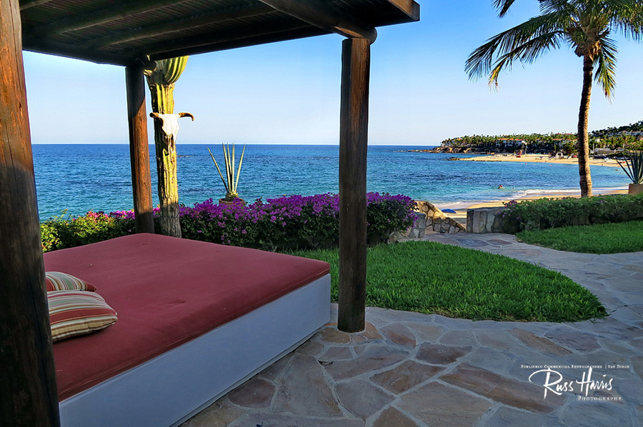 Outdoor patio with red lounge bed facing the ocean