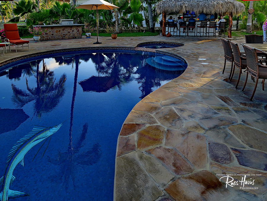 Blue bottom pool with rock siding and a swordfish mosiac tile in the pool